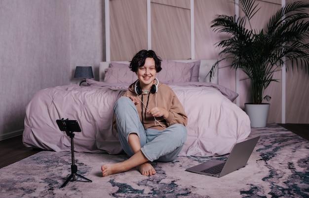 Una adolescente se sienta cerca de la cama y se comunica con sus amigos a través del teléfono.