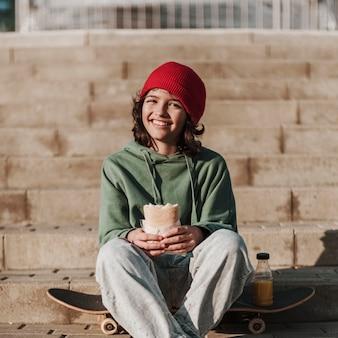 Adolescente sonriente almorzando en el parque en patineta