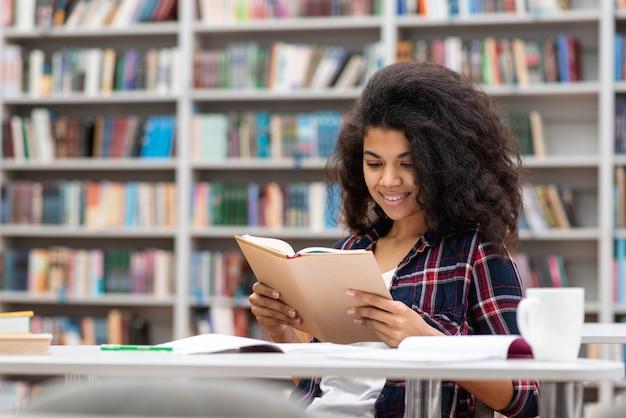 Adolescente sonriente de alto ángulo en la biblioteca