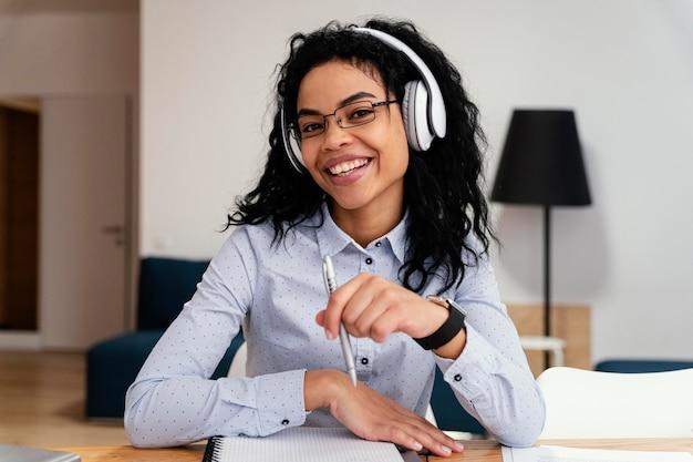 Adolescente sonriente en casa durante la escuela en línea con auriculares