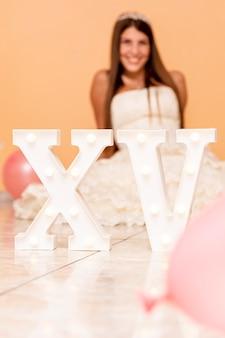 Adolescente sonriente celebrando su quinceañera con decoración divertida