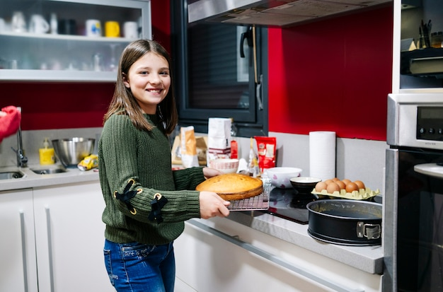 Un adolescente sonriente cocinando un bizcocho en la cocina