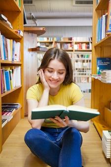Adolescente sonriente disfrutando de leer en el piso