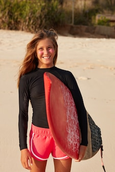 Adolescente sonriente encantada viste traje de neopreno o bañadores, sostiene una tabla de surf