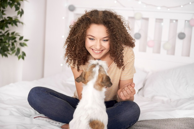 Adolescente sonriente jugando con su perro en el dormitorio