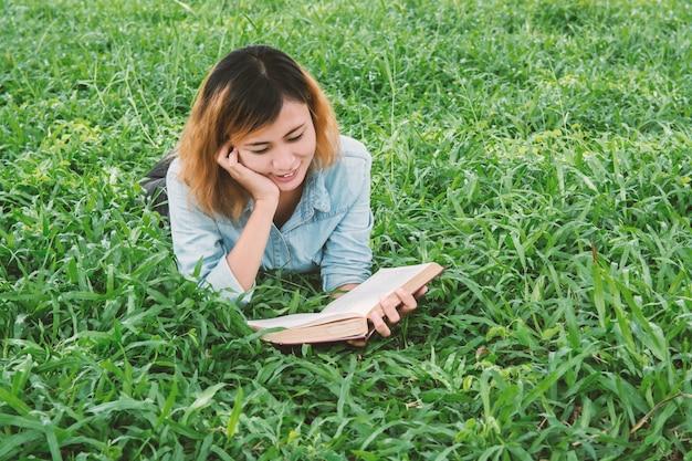 Adolescente sonriente leyendo una novela