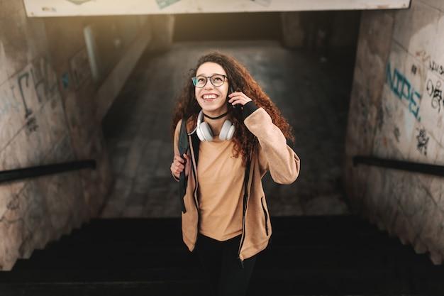 Adolescente sonriente con el pelo largo y rizado subiendo las escaleras en la estación de tren. auriculares alrededor del cuello