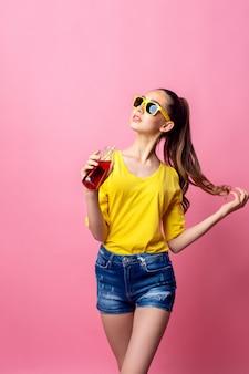 Adolescente sonriente de pie y bebiendo bebidas a través de paja
