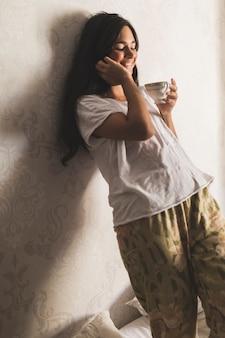 Adolescente sonriente que se inclina en el papel pintado que sostiene la taza