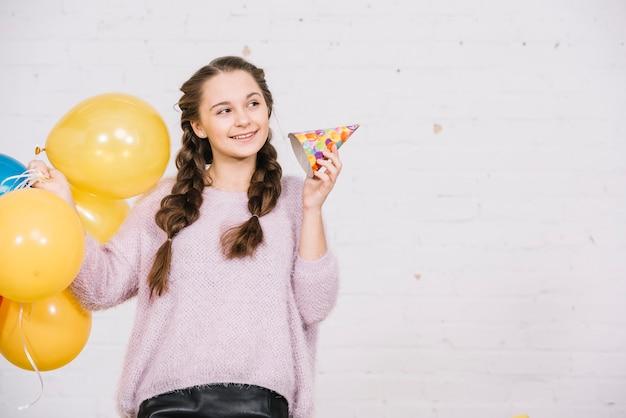 Adolescente sonriente que sostiene los globos y el sombrero del partido que miran lejos
