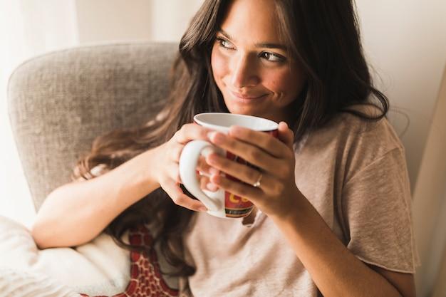 Adolescente sonriente que sostiene la taza de café