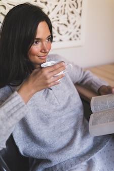 Adolescente sonriente que sostiene la taza y el libro de café
