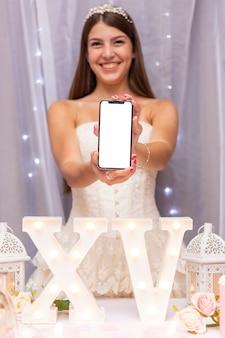 Adolescente sonriente sosteniendo un teléfono inteligente