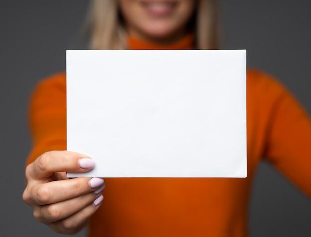 Una adolescente sonriente sostiene una maqueta de una gran hoja de papel en blanco con espacio para el texto.