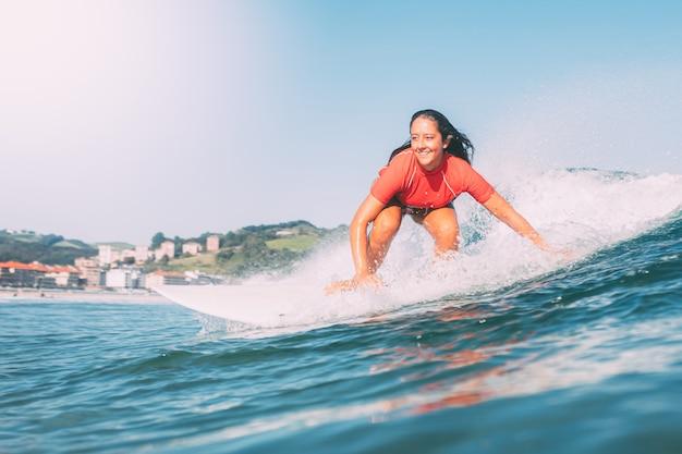 Adolescente sonriente surfeando, fotografiado desde el agua, en un día soleado