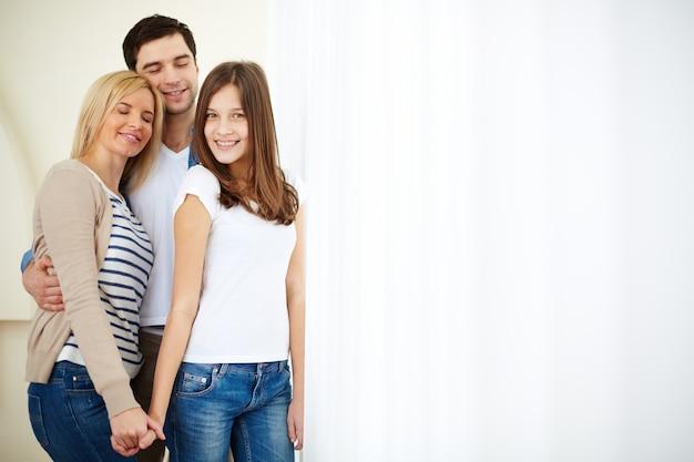Adolescente sonriente con sus padres Foto gratis
