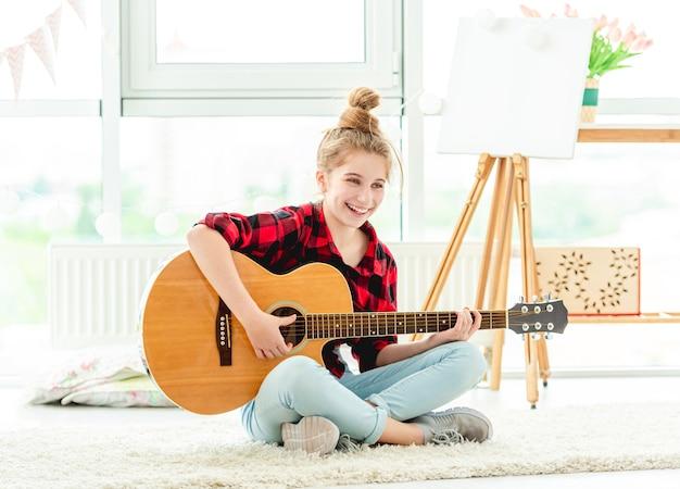 Adolescente sonriente tocando la guitarra