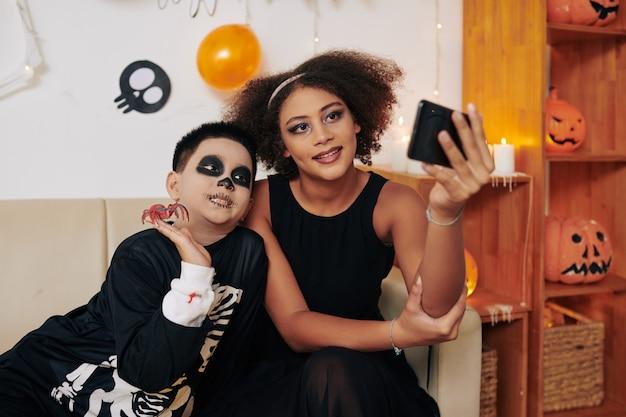 Adolescente sonriente tomando selfie con su hermano menor en la fiesta de halloween en casa