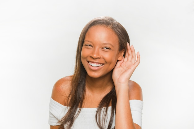 Adolescente sonriente tratando de escuchar sobre fondo blanco