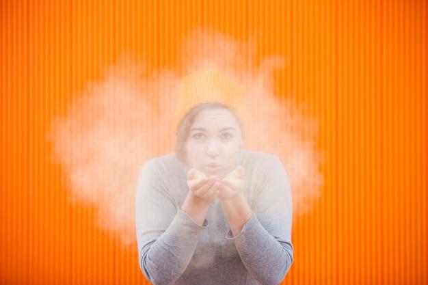 Adolescente soplando una nube de polvo de color en una pared naranja