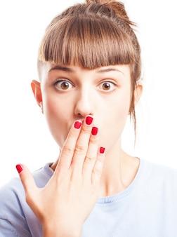 Adolescente sorprendida cubriéndose la boca con la mano