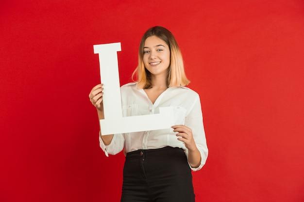 Adolescente sosteniendo la letra l