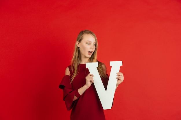 Adolescente sosteniendo la letra v