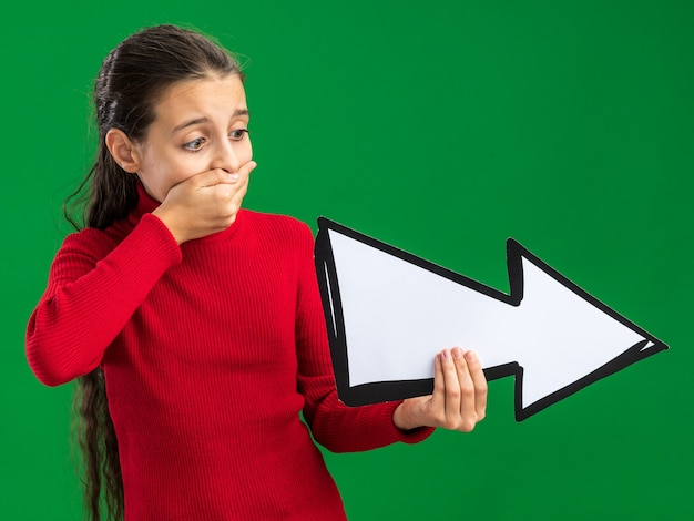 Adolescente sosteniendo y mirando la marca de flecha apuntando al lado manteniendo la mano en la boca aislada en la pared verde
