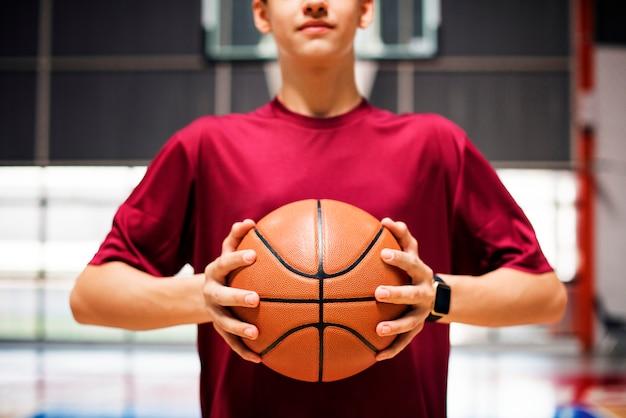 Adolescente sosteniendo una pelota de baloncesto en la cancha