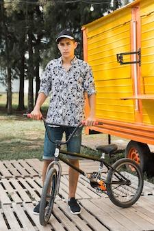 Adolescente sosteniendo su bicicleta en el parque