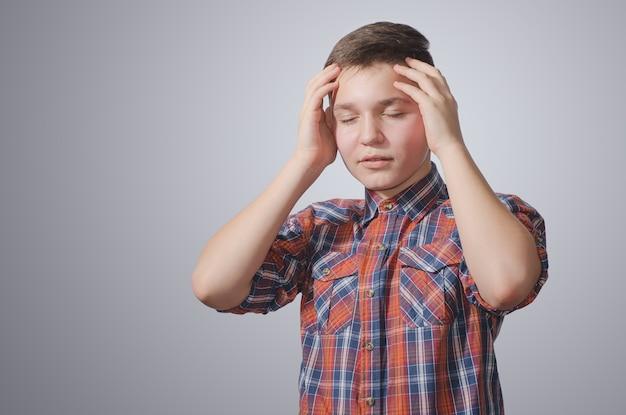Adolescente sosteniendo su cabeza con dolor. sobre una superficie gris-blanca con una camisa a cuadros