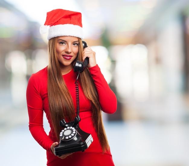 Adolescente sujetando un teléfono antiguo con fondo borroso