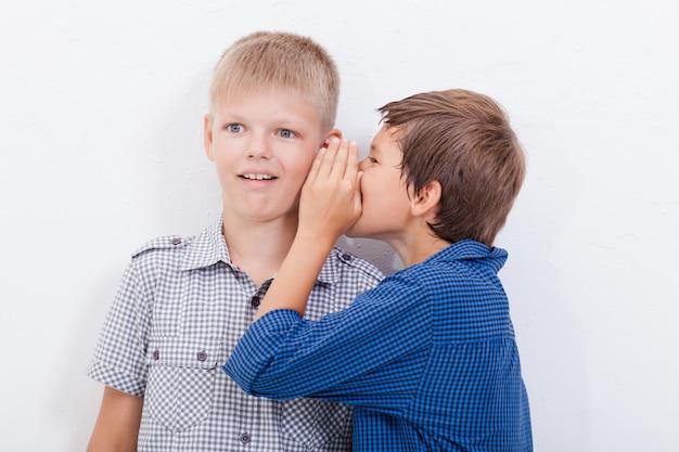 Adolescente susurrando al oído un secreto para friendl sobre fondo blanco.
