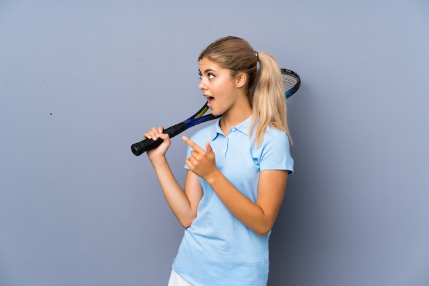 Adolescente tenista chica sobre pared gris sorprendido y apuntando hacia el lado