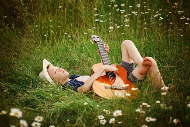 Adolescente tirado en el pasto con su guitarra acústica