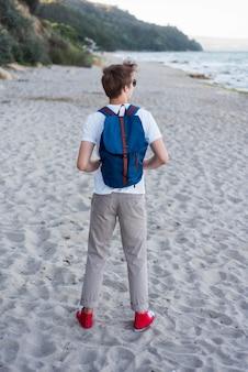Adolescente de tiro completo con mochila en la playa