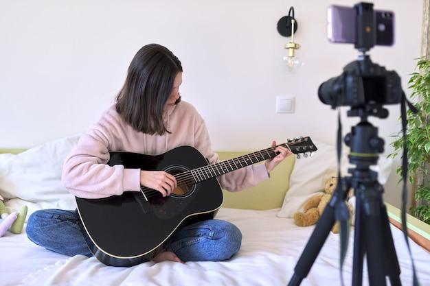 Adolescente tocando una guitarra acústica, hablando con seguidores, grabando video para canal, blog. aficiones para niñas, música, arte, educación, comunicación online con niños y adolescentes.