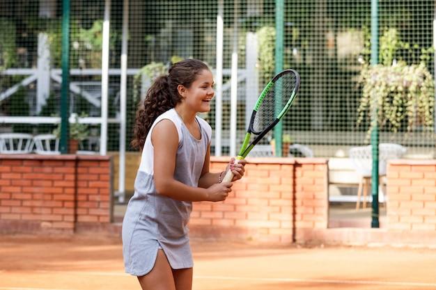 Adolescente en traje deportivo jugando al tenis