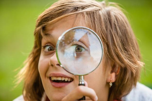Adolescente usa lupa para descubrir la naturaleza