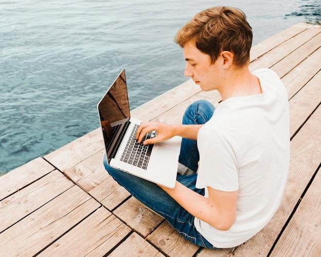 Adolescente usando laptop en el muelle