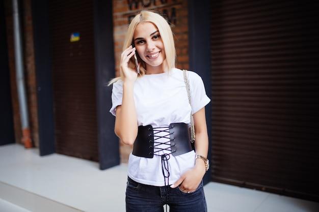 Adolescente usando teléfono celular. joven mujer rubia habla en un teléfono inteligente mientras camina por una calle de la ciudad.