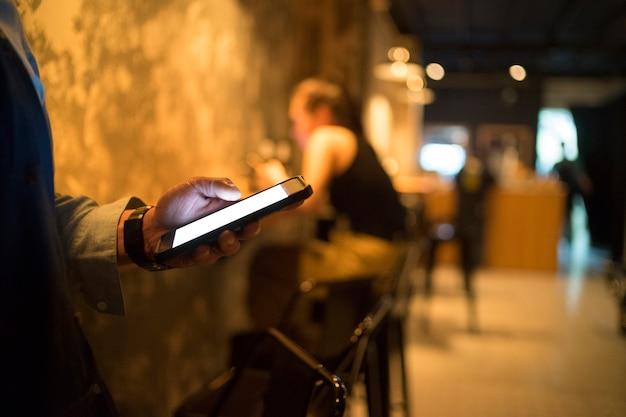 Adolescente use teléfono celular en el café