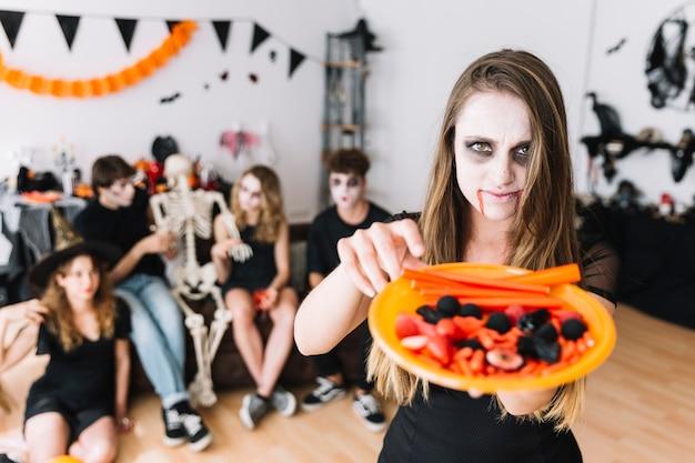 Adolescente con vampiro severo dando plato con dulces