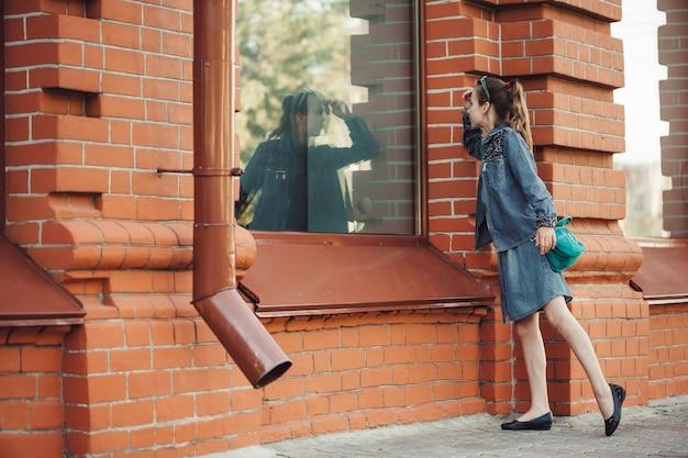 Adolescente en vestido de mezclilla azul mira en la ventana del edificio de ladrillo rojo al aire libre