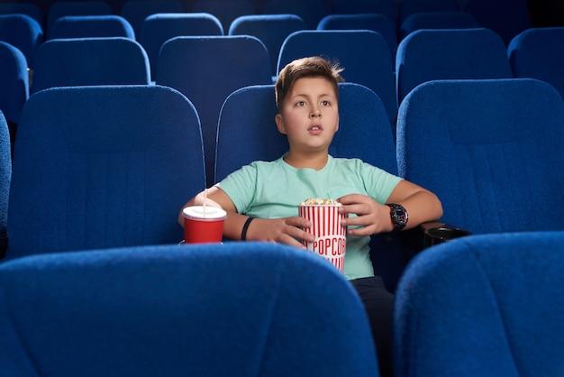 Adolescente viendo películas en el cine teatro.