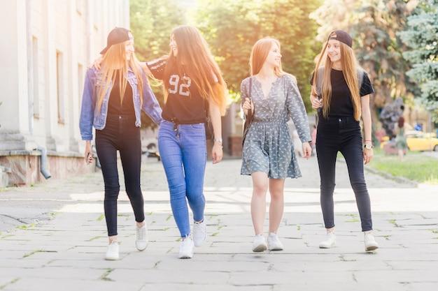 Adolescentes alegres caminando juntos después de la escuela