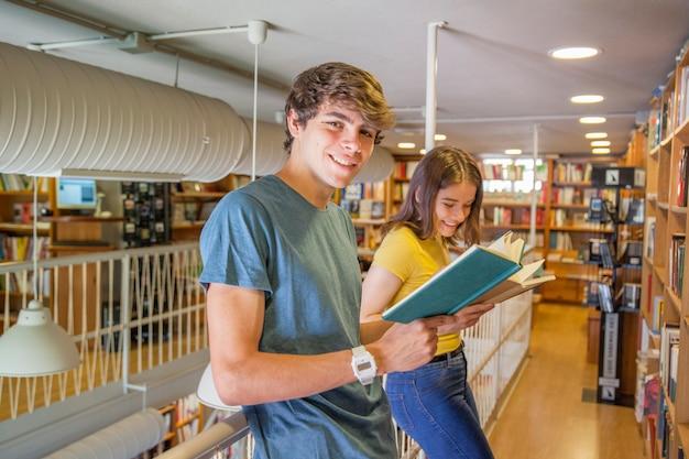 Adolescentes alegres disfrutando de lectura cerca de barandilla