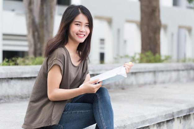 Las adolescentes asiáticas que leen la felicidad y la sonrisa del libro disfrutan de la educación en la universidad