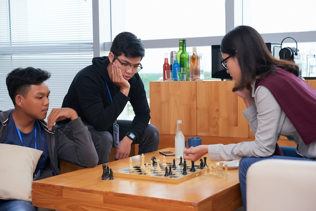 Los adolescentes asiáticos jugando al ajedrez con sus amigos viendo el partido
