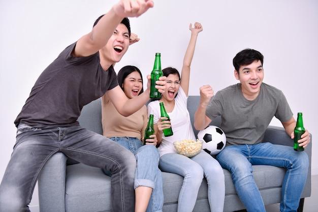 Adolescentes asiáticos viendo fútbol en televisión.